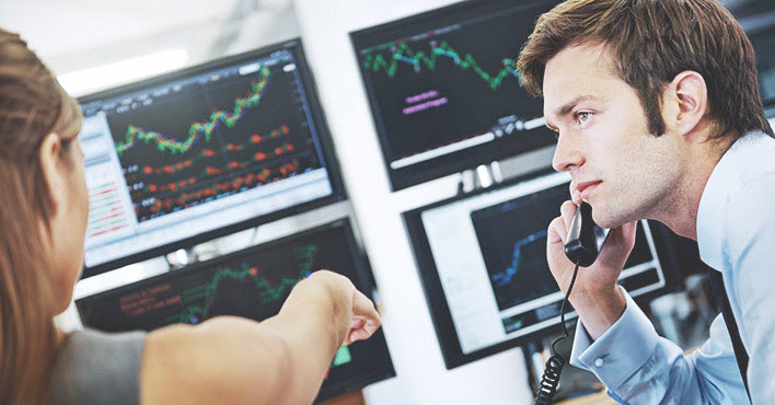 woman pointing at stock market screen
